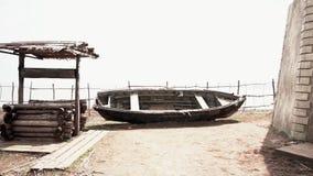 Η παλαιά ξύλινη βάρκα είναι στην ακτή ενός ποταμού βουνών footage Σπασμένη παλαιά βάρκα ψαριών σε μια ακτή άμμου της θάλασσας πλη απόθεμα βίντεο
