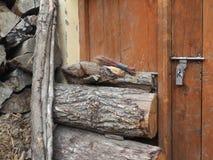 Η παλαιά ξύλινη πόρτα είναι καφετιά στον τοίχο του του χωριού σπιτιού, ξηροί σωροί των δέντρων, το καυσόξυλο συσσωρεύεται κοντά σ Στοκ φωτογραφία με δικαίωμα ελεύθερης χρήσης