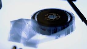 Η παλαιά ταινία 16mm βρίσκεται στο φωτισμένο πίνακα φιλμ μικρού μήκους