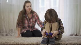 Η παλαιότερη αδελφή πορτρέτου επιπλήττει το μικρότερο αδερφό που παίζει με τη συνεδρίαση αυτοκινήτων παιχνιδιών στο πάτωμα στο χν απόθεμα βίντεο