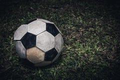 Η παλαιό σφαίρα ή το ποδόσφαιρο ποδοσφαίρου βάζει στην πράσινη χλόη για το λάκτισμα τα όμορφα μάτια φωτογραφικών μηχανών τέχνης δ Στοκ εικόνες με δικαίωμα ελεύθερης χρήσης