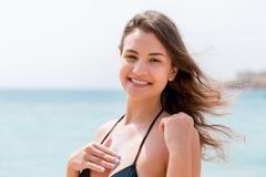 Η πανέμορφη γυναίκα εφαρμόζει την κρέμα ήλιων στο στήθος της με τα δάχτυλα στο υπόβαθρο θάλασσας στοκ φωτογραφίες