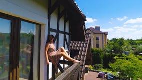 Η πανέμορφη γυναίκα κάθεται στην άκρη της χαλάρωσης θερινού χρόνου εξόδων μπαλκονιών ξένοιαστης απόθεμα βίντεο
