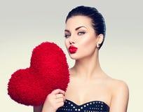 Η πανέμορφη γυναίκα με την καρδιά διαμόρφωσε το κόκκινο μαξιλάρι Στοκ Φωτογραφία