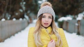 Η πανέμορφη γυναίκα στο κίτρινο σακάκι τυλίγεται που περπατά γύρω στο χιόνι E υπαίθρια όμορφες νεολαίες απόθεμα βίντεο