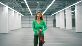 Η πανέμορφη κυρία κρατά ένα βιολί και ένα τόξο και ένα γέλιο απόθεμα βίντεο