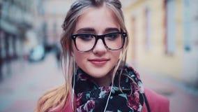 Η πανέμορφη νέα γυναίκα με τα ακουστικά και στα μαύρα γυαλιά κοιτάζει γοητευτικά δεξιά προς τη κάμερα Θηλυκό πορτρέτο φιλμ μικρού μήκους