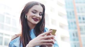 Η πανέμορφη νέα γυναίκα χρησιμοποιεί το τηλέφωνό της και ευτυχώς το χαμόγελο Μοντέρνος κοιτάξτε, κόκκινα χείλια, να διαπερνήσει μ φιλμ μικρού μήκους
