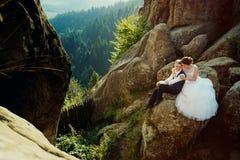 Η πανέμορφη νύφη αγκαλιάζει μαλακά την πλάτη νεόνυμφων γοητείας χαμόγελου καθμένος στο βράχο στο υπόβαθρο στοκ φωτογραφία με δικαίωμα ελεύθερης χρήσης