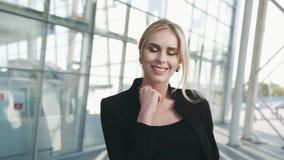 Η πανέμορφη ξανθή γυναίκα σε μια μαύρη εξάρτηση κοιτάζει δεξιά προς τη κάμερα και μοιράζεται ένα όμορφο χαμόγελο Τερματικό αερολι φιλμ μικρού μήκους
