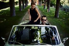 Η πανέμορφη πλούσια γυναίκα αισθάνεται τόσο ευτυχής ενώ αυτοί που οδηγούν στο καμπριολέ με το βέβαιο όμορφο άνδρα brunette Στοκ Εικόνα