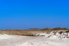 Η πανοραμική άποψη πέρα από τη χλόη κάλυψε την άμμο στην οικοδόμηση σύνθετη στην απόσταση στοκ φωτογραφία με δικαίωμα ελεύθερης χρήσης