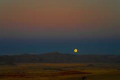 Η πανσέληνος ανέρχεται πέρα από τον αμμόλοφο στην έρημο Namib Στοκ Φωτογραφία