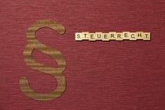 Η παράγραφος σημαδιών στο υπόβαθρο χρώματος κλαρέ Λέξη σε γερμανικό Steuerrecht στοκ εικόνα με δικαίωμα ελεύθερης χρήσης