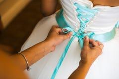 Η παράνυμφος βοηθά να δέσει ένα τόξο σε ένα εορταστικό άσπρο φόρεμα της νύφης στη ημέρα γάμου Στοκ Φωτογραφίες