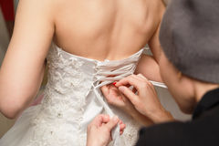Η παράνυμφος βοηθά τη νύφη για να ντύσει την κορδέλλα Στοκ φωτογραφία με δικαίωμα ελεύθερης χρήσης