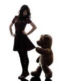 Η παράξενη νέα γυναίκα και κακοήθης teddy αντέχουν τη σκιαγραφία Στοκ φωτογραφίες με δικαίωμα ελεύθερης χρήσης