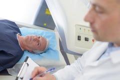 Η παραγωγή γιατρών σημειώνει ενώ ασθενής κάτω από τη μηχανή ανίχνευσης στοκ εικόνες