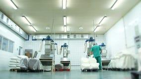 Η παραγωγή, εργαστήριο εργοστασίων, ο εργαζόμενος φορτώνει τη ζάχαρη και την ξηρά κρέμα από τις τσάντες σε μια ειδική μηχανή υπάρ απόθεμα βίντεο