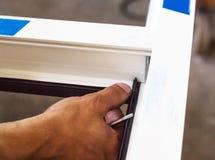Η παραγωγή των παραθύρων PVC, ο εργαζόμενος εγκαθιστά το σφραγίζοντας λάστιχο στο πλαίσιο PVC, κινηματογράφηση σε πρώτο πλάνο, χέ στοκ φωτογραφία με δικαίωμα ελεύθερης χρήσης