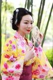 Η παραδοσιακή ασιατική ιαπωνική όμορφη γυναίκα γκείσων φορά τη λαβή κιμονό που ένας ανεμιστήρας παραδίδει επάνω ένα καλοκαίρι Στοκ Εικόνες