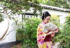 Η παραδοσιακή ασιατική ιαπωνική όμορφη γυναίκα γκείσων φορά τη λαβή κιμονό που ένας ανεμιστήρας παραδίδει επάνω μια θερινή φύση Στοκ εικόνες με δικαίωμα ελεύθερης χρήσης