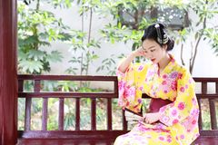 Η παραδοσιακή ασιατική ιαπωνική όμορφη γυναίκα γκείσων φορά τη λαβή κιμονό που ένας θαυμαστής κάθεται σε έναν πάγκο σε έναν κήπο  Στοκ Φωτογραφία