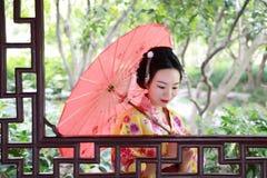 Η παραδοσιακή ασιατική ιαπωνική όμορφη νύφη γυναικών γκείσων φορά το κιμονό με την κόκκινη ομπρέλα παραδίδει επάνω μια θερινή φύσ Στοκ Εικόνα