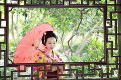 Η παραδοσιακή ασιατική ιαπωνική όμορφη νύφη γυναικών γκείσων φορά το κιμονό με την κόκκινη ομπρέλα παραδίδει επάνω μια θερινή φύσ Στοκ φωτογραφία με δικαίωμα ελεύθερης χρήσης