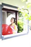 Η παραδοσιακή ασιατική ιαπωνική όμορφη νύφη γυναικών γκείσων φορά το κιμονό με την κόκκινη ομπρέλα παραδίδει επάνω μια θερινή φύσ Στοκ Εικόνες
