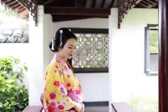 Η παραδοσιακή ασιατική ιαπωνική όμορφη νύφη γυναικών γκείσων φορά το κιμονό με την κόκκινη ομπρέλα παραδίδει επάνω μια θερινή φύσ Στοκ εικόνα με δικαίωμα ελεύθερης χρήσης