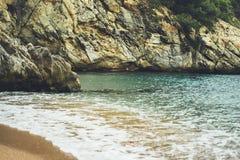 Η παραλία ακτών στην ηλιόλουστη δύσκολη ακτή υποβάθρου ημέρας, χρυσή στενή επάνω θαμπάδα άμμου, τουρισμός χαλαρώνει το ήρεμο πρότ Στοκ Εικόνα