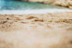 Η παραλία ακτών στο ηλιόλουστο υπόβαθρο ημέρας της θάλασσας και του ουρανού, χρυσή στενή επάνω θαμπάδα άμμου, τουρισμός χαλαρώνει Στοκ Εικόνα