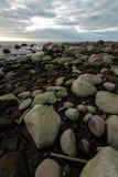 Η παραλία λίθων κατά τη διάρκεια ενός νεφελώδους ηλιοβασιλέματος με τ στοκ φωτογραφία με δικαίωμα ελεύθερης χρήσης