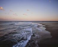 Η παραλία πλάγιας όψης και το αργά το απόγευμα ελαφρύ τοπίο κυμάτων χρωματίζουν το Νιουκάσλ Νότια Νέα Ουαλία Αυστραλία στοκ εικόνες με δικαίωμα ελεύθερης χρήσης