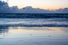 Η παραλία στο ηλιοβασίλεμα με τα πλησιάζοντας κύματα - εικόνα στοκ φωτογραφία με δικαίωμα ελεύθερης χρήσης
