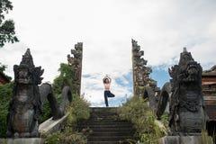 Η παραμονή γυναικών στο yoge θέτει στην παλαιά είσοδο ναών σκαλοπατιών πετρών στοκ φωτογραφία με δικαίωμα ελεύθερης χρήσης