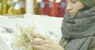 Η Παραμονή Πρωτοχρονιάς, κορίτσι στο κατάστημα επιλέγει τις διακοσμήσεις Χριστουγέννων, παιχνίδια, σφαίρες, κώνοι φιλμ μικρού μήκους