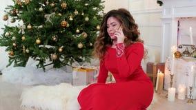 Η Παραμονή Πρωτοχρονιάς, μια όμορφη νέα γυναίκα στο προκλητικό φόρεμα διακοπών, Χριστούγεννα επιθυμεί με τους φίλους που μιλούν σ απόθεμα βίντεο