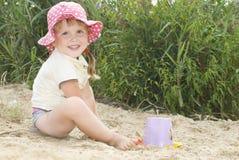 Η παραλία στη λίμνη στην άμμο ένα μικρό κορίτσι σε ένα καπέλο playin Στοκ Φωτογραφία