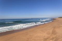 Η παραλία στρώνει με άμμο τον μπλε ωκεανό Στοκ Φωτογραφίες