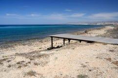 Η παραλία της Kato Πάφος με την ξύλινη αποβάθρα, χαλαρώνει τη θέση στην παραλία της Κύπρου Στοκ Εικόνες