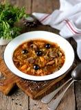Η παραδοσιακή ρωσική σούπα solyanka έκανε από τα φρέσκων και ξηρών μανιτάρια λάχανων, με τις ελιές, το λεμόνι και τις κάπαρες Στοκ Εικόνες