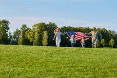 Η πατριωτική οικογένεια με τις τεράστιες ΗΠΑ σημαιοστολίζει υπαίθρια Στοκ Εικόνα
