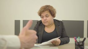 Η παχουλή γυναίκα στην επίσημη συνεδρίαση ένδυσης στον πίνακα στο γραφείο που κάνει τη γραφική εργασία Χέρι ατόμων που παρουσιάζε φιλμ μικρού μήκους