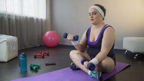Η παχύσαρκη γυναίκα που ενισχύει εύκολα τους μυς με τους αλτήρες, θέλει να χάσει το βάρος απόθεμα βίντεο