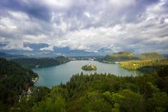 Η παλαιά εκκλησία στο μικρό νησί στη μέση της λίμνης άνωθεν με το δραματικό ουρανό, αιμορράγησε τη λίμνη, Σλοβενία Στοκ Φωτογραφία