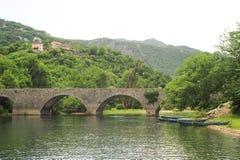 Η παλαιά σχηματισμένη αψίδα γέφυρα πετρών του Rijeka Crnojevica στοκ φωτογραφία