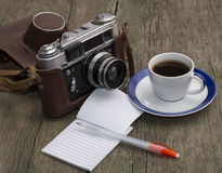 Η παλαιοί κάμερα, ο καφές και το σημειωματάριο με τη λαβή σε έναν ξύλινο Στοκ Εικόνες
