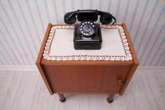 Μαύρο ντεμοντέ περιστροφικό τηλέφωνο πινάκων σε ένα κομμάτι των επίπλων Στοκ Εικόνες